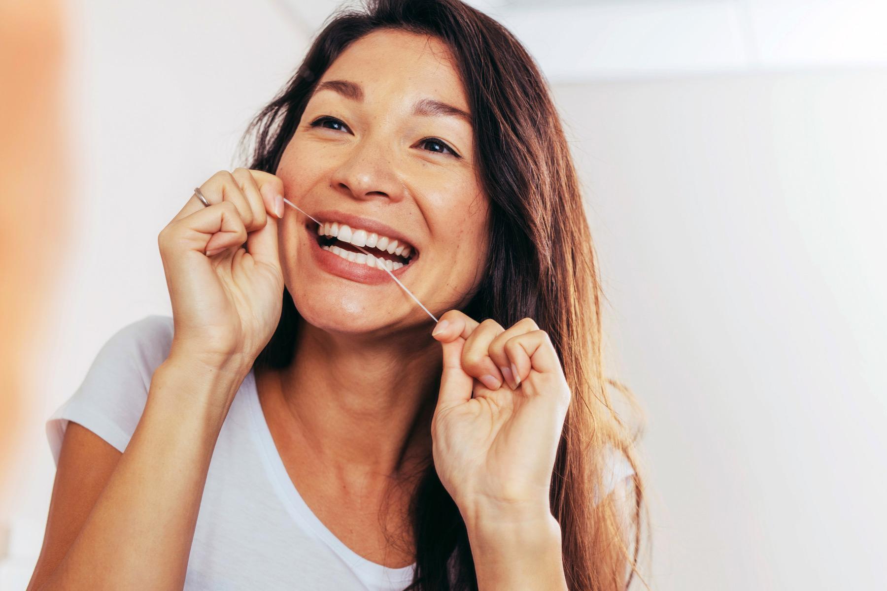 photo of woman flossing her teeth